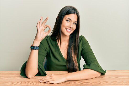 Young brunette woman wearing casual clothes sitting on the table smiling positive doing ok sign with hand and fingers. successful expression.