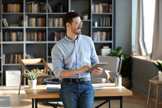 Entrepreneur standing in modern luxury office room distracted from work, business task and planning holding tablet device looks out the window feels happy, visualizing future, business vision concept