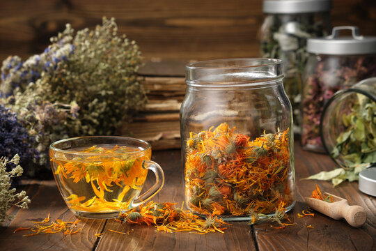 Cup of healthy marigold tea, glass jar of dry calendula flowers. Jars of medicinal herbs and old books on background.  Alternative medicine.