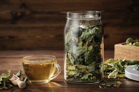 Cup of healthy tea with Linden tree flowers, jar of dry flowers and leaves of lime or Tilia cordata tree. Treatment for cold and flu.