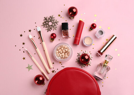 Flat lay composition with decorative cosmetic products on pink background. Winter care
