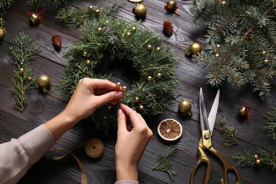 Florist making beautiful Christmas wreath at black wooden table, closeup