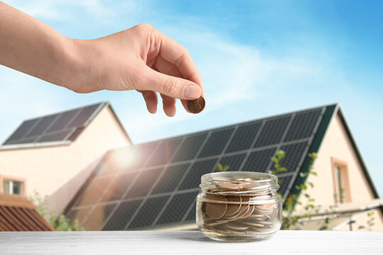 Woman putting coin into jar against house with installed solar panels on roof, closeup. Economic benefits of renewable energy