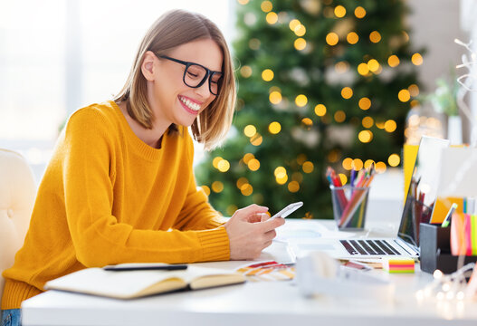 Delighted freelancer using smartphone on Christmas day.