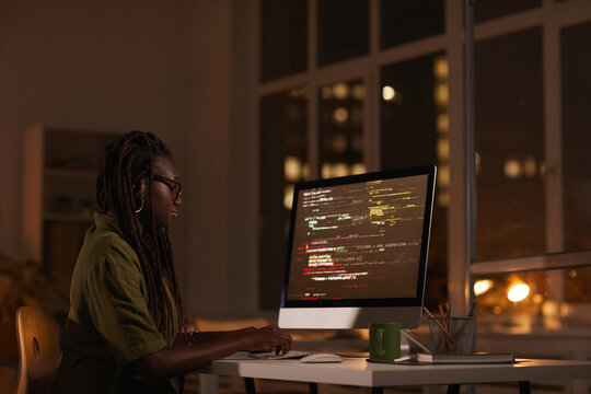 Side view portrait of contemporary African-American woman looking at computer screen and writing code while working late at night, copy space