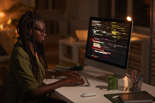 Side view portrait of contemporary African-American woman writing code and looking at computer screen while working in dark office, copy space