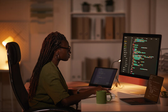 Side view portrait of contemporary African-American woman writing code and looking at computer screen while working in dim office, copy space