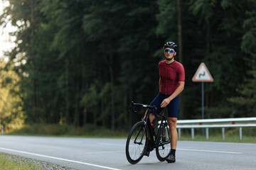 Young cyclist with muscular body relaxing on road