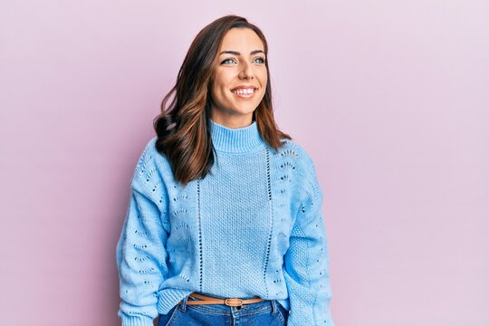 Young brunette woman wearing casual winter sweater over pink background looking away to side with smile on face, natural expression. laughing confident.