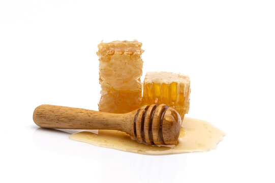 Honey In a glass cup and a honeycomb On a wooden background