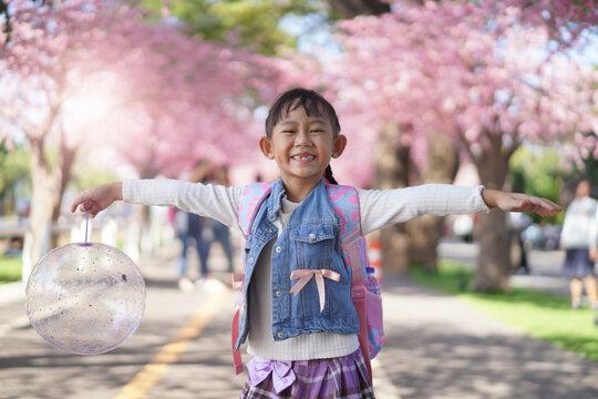 Asian little girl in garden under the blossom sakura tree background