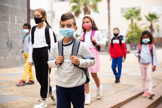Focused hispanic tweenager in medical face mask with backpack going to school lessons on warm autumn day. New lifestyle during coronavirus pandemic.