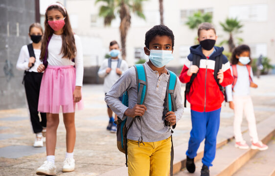 African american tween schoolboy in protective mask with backpacks going to school lessons on fall day. Back school concept during pandemic