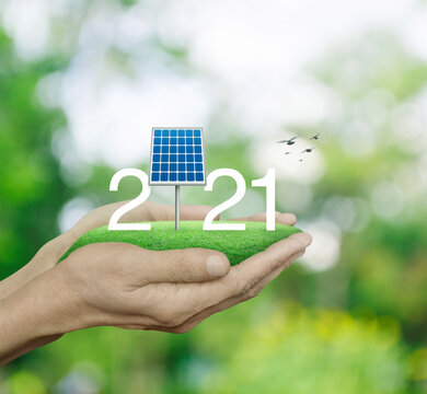 2021 white text with solar cell on green grass field in man hands over blur green tree, Happy new year 2021 ecological cover concept