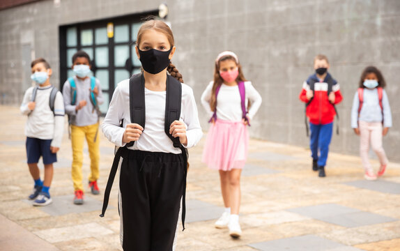 Confident teen girl in protective mask walking outside school building on spring day, going to lessons. Concept of necessary precautions in COVID pandemic.