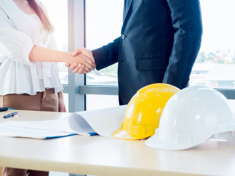 Businessman in suit, engineering or architect and woman shaking hands on blueprint and yellow and white safety hard hat on desk.
