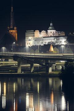 The Ducal Castle (Zamek Ksiazat Pomorskich) and Cathedral in Szczecin reflected in Odra River at foggy night, Poland.