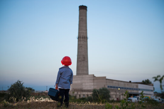 one little worker boy in red helmet standing on factory plant industrial company building with pipe holding tool box with copy space