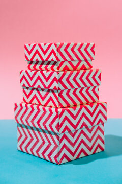 Stack of bright striped gift boxes on a blue and pink pastel background. Concept of a holiday, Christmas, new year or birthday. Close up, pop art