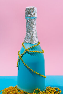 Champagne bottle with golden Christmas decorations on abstract pastel colorful pink and blue backdrop. New Year Party aesthetic. Close up, still life