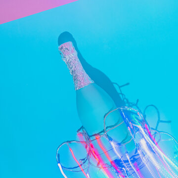 Champagne bottle with Christmas lights decoration and long trail on abstract pastel colorful pink and blue backdrop. New Year Party aesthetic. Vaporwave holographic art. Flat lay, top view.