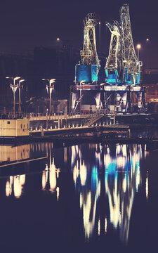 Illuminated port cranes on Lasztownia Island in Szczecin at a foggy night, color toning applied, Poland.