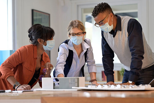 Team of architects working on project, wearing face mask in office