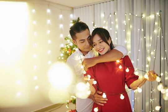 Beautiful young couple in love standing in living room tangled in Christmas lights