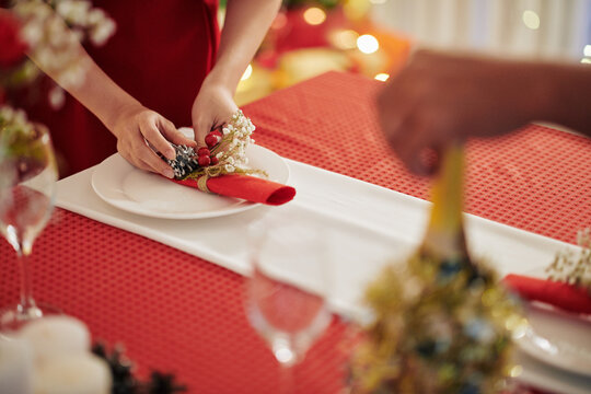 Close-up image of woman putting decorated napkin on table when preparing for Chrismas celebration at home