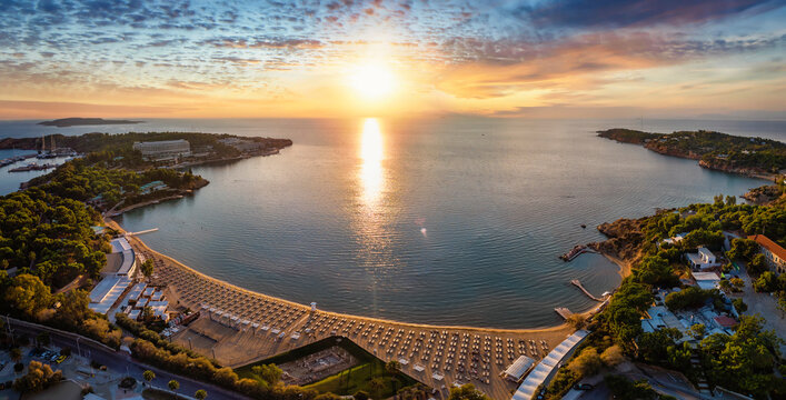 Panoramic aerial view of the popular celebtrity beach of Astir, Vouliagmeni district in south Athens, Greece, during sunset time