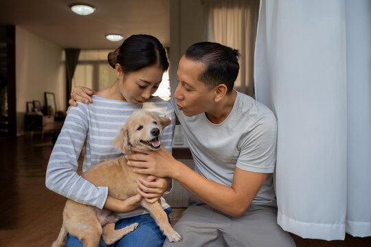 Young adult Asian couple holding a puppy with home interior in background. 30s mature man kissing a dog pet in arms of woman. Husband and wife living together in the house. Modern family happiness