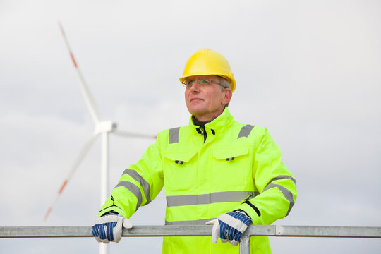 Mature engineer with hard hat and protective clothing in front of blurred wind turbine