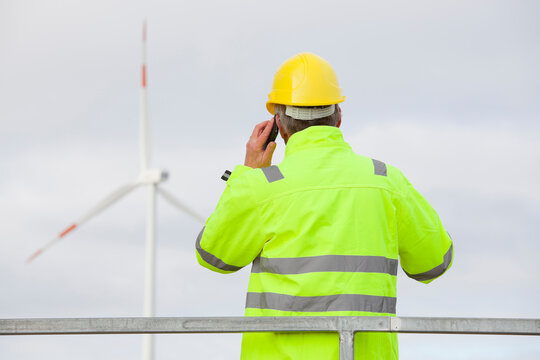 Engineer with protective work wear talking on mobile phone in front of a wind turbine