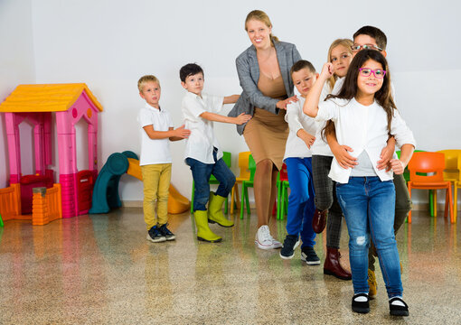 Glad cheerful positive female teacher playing circle game with children in classrom