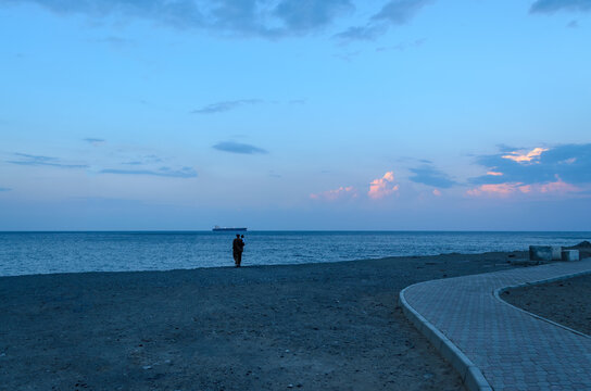 An Omani Man & child looking at a ship in the distance in the evening at Darsait beach, Muscat, Oman.