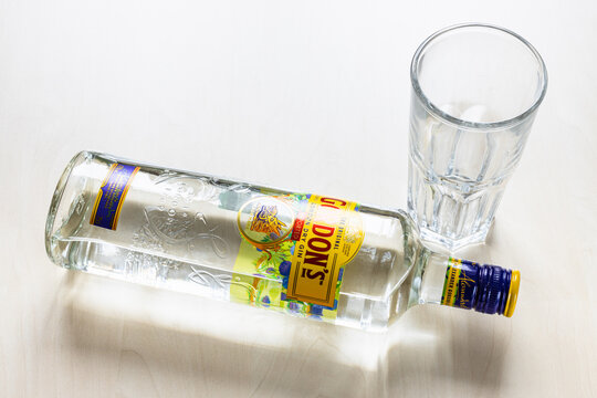 MOSCOW, RUSSIA - NOVEMBER 4, 2020: top view of lying bottle of Gordon's London Dry Gin and empty glass on light brown board. Gordon's is brand of London dry gin first produced in 1769.
