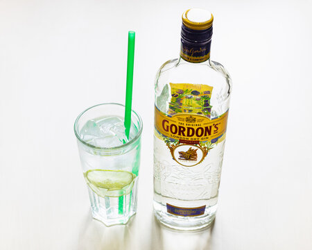 MOSCOW, RUSSIA - NOVEMBER 4, 2020: above view of bottle of Gordon's London Dry Gin and highball glass with prepared gin and tonic cocktail on light brown board. Gordon's gin first produced in 1769.