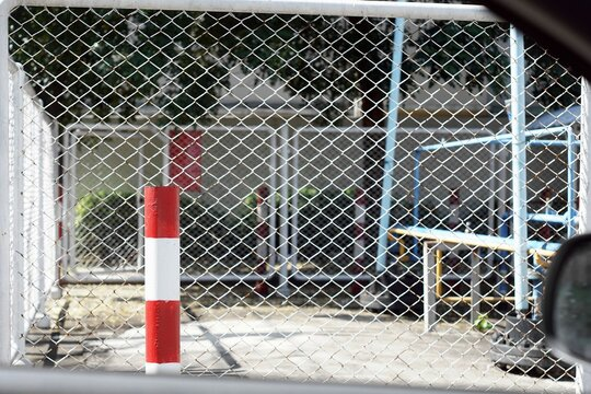 Close-UP a red-white pillar to sign danger  with a Steel mesh fence look out of the car.