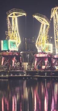 Illuminated port cranes on Lasztownia Island in Szczecin at a foggy night, Poland.