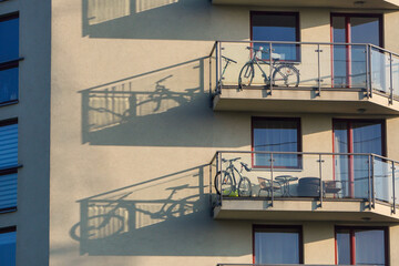 Storage of bicycles and scooters on an open balcony on a Sunny day in apartment building, street view. Active recreation and sports in life. The play of light and shadow on the wall of the building. Fotomurales