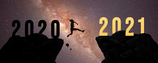Silhouette man jump between 2020 and 2021 years with sunset background, Success new year concept. Wall mural