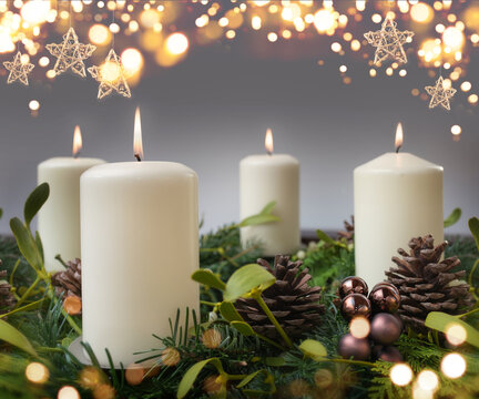 Four burning candle in a advent wreath of fir branches with christmas ornament and golden bokeh. Festive background with short depth of field for the christmas season with space for your text.