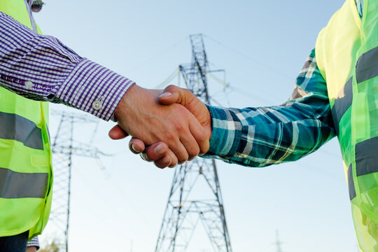 Low angle side view of crop anonymous male engineers shaking hands while standing against modern electric high voltage construction