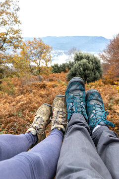 Couple sitting in the forest, only the feet and shoes are visible. Unrecognizable persons.
