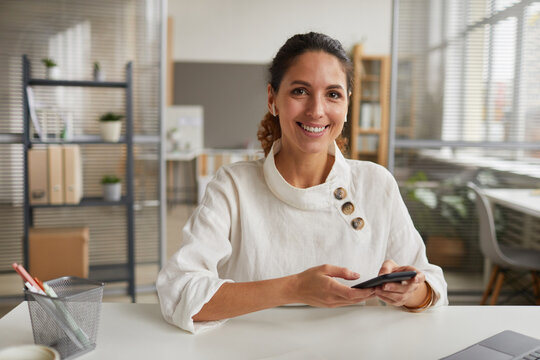 Portrait of smiling businesswoman holding smartphone and looking at camera while sitting at desk in office, copy space