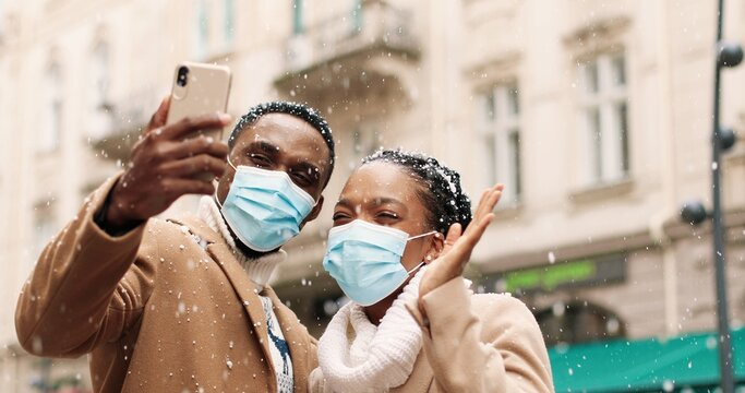 Close up portrait of happy family calling on video on smartphone on snowy street on Christmas Eve congratulating relatives. Man and woman in masks in quarantine wish happy new 2021 year on video chat
