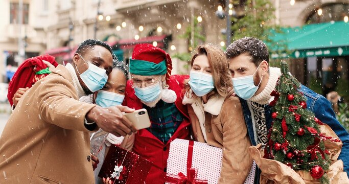 Santa Claus in mask hugs African American and Caucasian young people while taking selfie photo on cellphone. Portrait of males ad females friends take pictures with Santa on snowy street. X-mas spirit