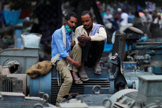 Men wearing protective face masks on their chins watch a video on a mobile phone as they sit at a second-hand motor parts market in the old quarters of Delhi