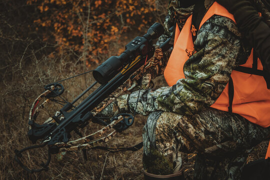 Hunter holding a crossbow with a night vision scope, close-up, soft focus