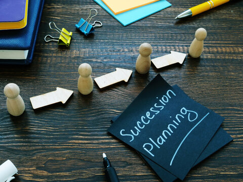 Succession planning sign and figurines with arrows.